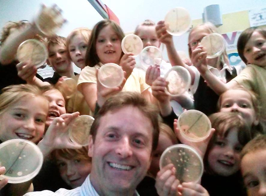 Donald with a group of primary school children holding up agar plates of bacteria